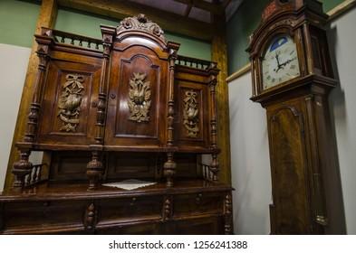 November, 2018 - The Velsky Museum. Antique wooden dresser and floor clock. Russia, Arkhangelsk region, Velsk