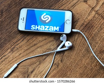 November 2019 Parma, Italy: Smartphone with Shazam app on tablet close-up, headphones on wooden table. Shazam mobile application