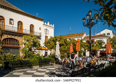 NOVEMBER 21, 2017 - MARBELLA, SPAIN. People having lunch outside in a public plaza on a sunny day. Traditional white buildings.