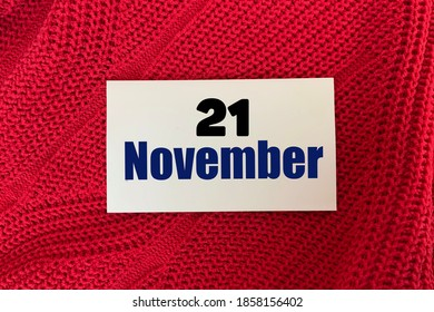 November 21 on a sticker on a red knitted background.Autumn .Calendar for November.