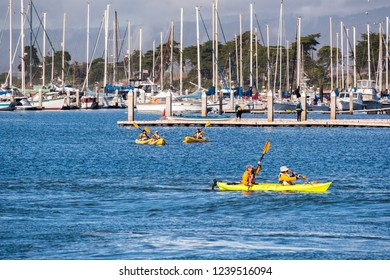 November 22, 2018 Moss Landing / CA / USA - People kayaking in Elkhorn Slough on a sunny day; yachts moored in the marina visible in the background