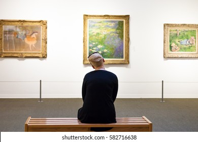 "November 25: A woman is sitting on a bench and looking at the painting by Claude Monet ""Lilies"", in the Museum of Art, Tel Aviv, Israel, November 25, 2016"