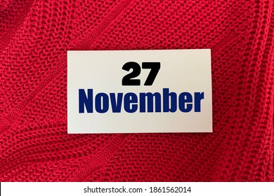 November 27 on a sticker on a red knitted background.Autumn .Calendar for November.
