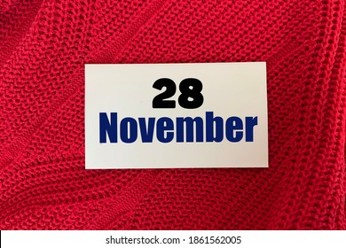 November 28 on a sticker on a red knitted background.Autumn .Calendar for November.