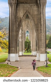 November 3, 2018 - Portland, Oregon: Father and young daughter under the support structures of St. John's Bridge in Portland, Oregon that Resemble a Cathedral at Cathedral Park