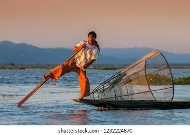 November 30, 2015. Traditional Burmese fishermen with fishing net at Inle lake in Myanmar famous for their distinctive one legged rowing style, Nyaung Shwe, Inle, Taunggyi, Shan State, Myanmar.