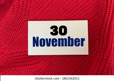 November 30 on a sticker on a red knitted background.Autumn .Calendar for November.