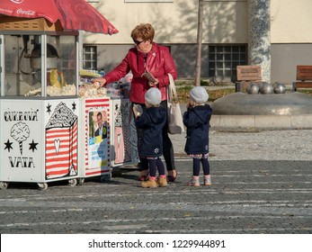 November 6, 2018, Trnava, Slovakia The old mum buys grandchildren of the popcorn in the street of a street vendor.On the wall of the stand is a poster with a candidate for the mayor of the city.