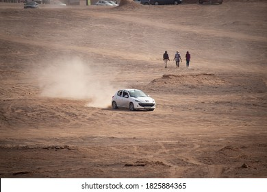 November 8, 2018- Iran, Kerman- Kalut Shahdad Desert, Doing desert safari on sandy desert ground with a white 206 peugeot car with floated sand in the air at the back of the car