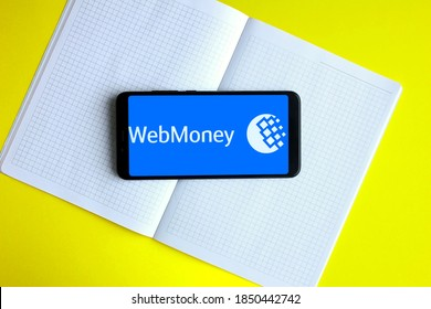 November 8, 2020, Moscow, Russia. Electronic wallet WebMoney on the smartphone screen. Yellow background, telephone and notebook.