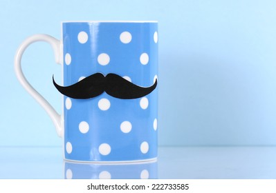 November fund raising for mens health awareness charity with mustache on blue polka dot coffee mug cup on blue background, with copy space.