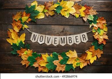 November lettering on paper cardboard eco garland, autumn leafs wreath, dark brown rustic barn wood background.