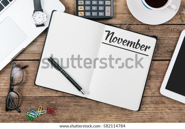 November text in note book on office desk with electronic devices, computer and paper, wood table from above, concept image for blog title or header image.