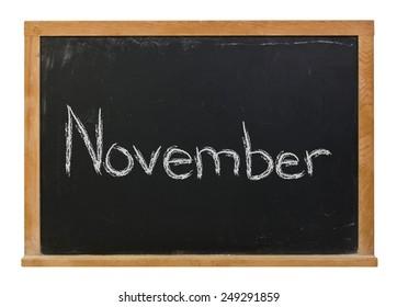 November written in white chalk on a black wood framed chalkboard isolated on white