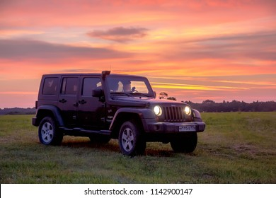 Novgorod region, Russia, July 19, 2018: Jeep Wrangler in the field at sunrise. Wrangler is a compact four wheel drive off road and sport utility vehicle