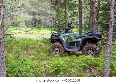NOVGOROD REGION, RUSSIA - JULY 9, 2015: The modern quad bike parked at the forest in summer day