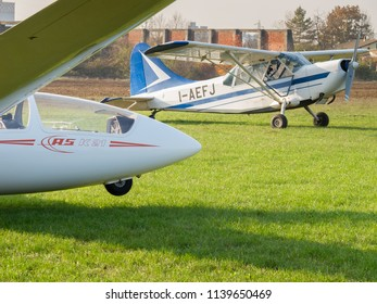 Novi Ligure, Alessandria, Italy - November 12 2011: ASK-21 sailplane (glider) on grass runway of local airfield and tow plane Stinson L-5 Sentinel ready for takeoff. Gliders fly (soar) without engine
