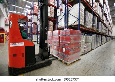 NOVI LIGURE, ITALY - 21 NOVEMBER 2012: An employee uses a forklift truck to maneuver a pallet load of Campari boxes inside the warehouse at Davide Campari-Milano SpA's factory.