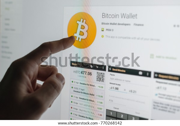 NOVI SAD, SERBIA - December 7, 2017: Man installing Bitcoin wallet application. Bitcoin virtual cryptocurrency just reached $14,000 value.