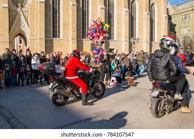 Novi Sad, Serbia Decemeber 30, 2017: Motorcyclists  dressed as Santa Claus drive through the center of Novi Sad and share sweets with children.