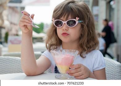 Novi Sad, Serbia - May 02, 2017: Little girl with sunglasses on her head eating icecream
