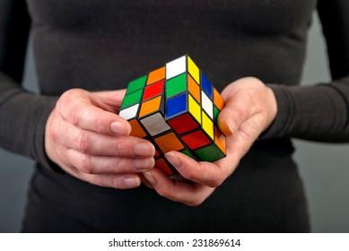 NOVI SAD, SERBIA - NOVEMBER 17, 2014: Woman solving Rubik's Cube invented by a Hungarian architect Erno Rubik in 1974