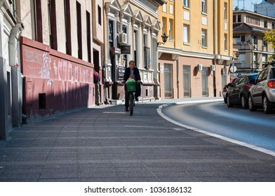 Novi Sad , Serbia - october 9, 2014: Woman rides a bicycle on the sidewalk. Urban background