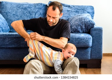 Novice father changing clothes to his baby with effort in the living room of his house.