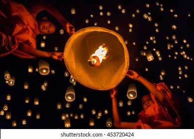 Novice monk lights floating lanterns made of paper in Loi Krathong or Loy Krathong day.