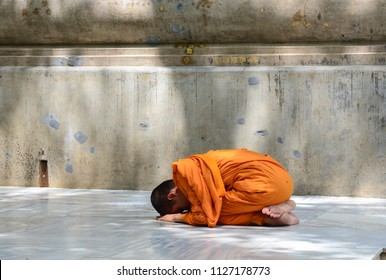 A novice monk praying at a Buddhist temple.