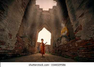 Novice monk  is reading a book to learn Dharma in front of an old Buddha image in a old temple.
