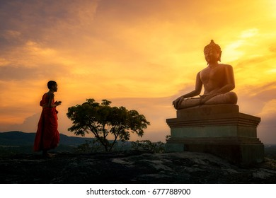 Novice monk standing in meditation in front of Buddha statue