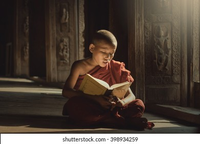 Novice reading book with lighting in temple,Mandalay,Myanmar.