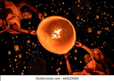 Novices monk lights floating lanterns made of paper in Loi Krathong or Loy Krathong day, Loi Krathong or Loy Krathong day is one of the most important days of Thai people.