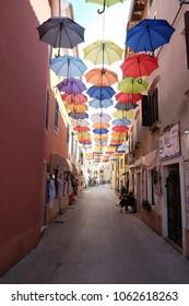 NOVIGRAD, CROATIA - SEPTEMBER 29: Umbrellas on a shopping street in the old town of  Novigrad, Croatia, on September 29, 2017.