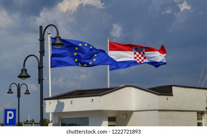 Novigrad, Istria, Croatia. August 2018. At the port, next to a lamp post, the flags of Europe and Croatia. The sea-eath spreads them and makes them nervously move.