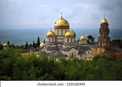 Novo-Athos Simon-Kananitsky monastery in Abkhazia. Monastery with palm trees and golden domes on a sunny day. Provaslavny monastery on the seashore. Top view of the Novo-Athos monastery.