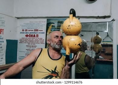Novograd, Volyn / Ukraine - March 31 2009: Senior man working out using kettlebell in rural gym