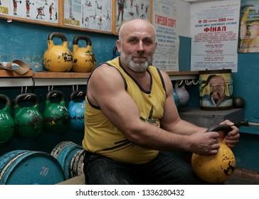 Novograd, Volyn / Ukraine - March 31 2009: Senior man posing with kettlebell in rural gym