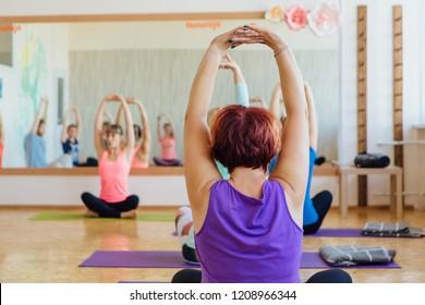 Novokuznetsk, Kemerovo region, Russia - 11 August 2018: Women of different age doing yoga exercises with teacher on yoga class.