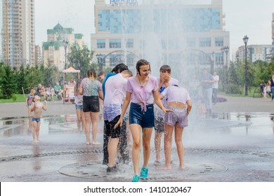 Novokuznetsk, Kemerovo Region, Russia - August 04, 2018: Happy teenagers splashing in a water of a city fountain and enjoying the cool streams of water in a hot day. Hot summer.