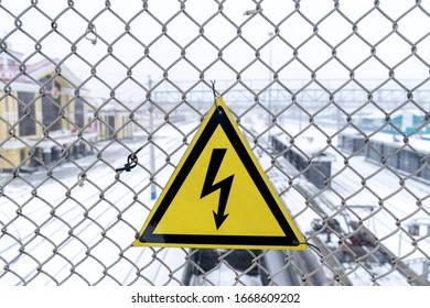 Novokuznetsk, Kemerovo region, Russia. March 09, 2020. Yellow sign, dangerous, high voltage on the grid against the background of the railway station