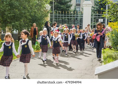 NOVOKUZNETSK, KEMEROVO REGION, RUSSIA - SEPTEMBER, 1, 2016: Meeting with the first-grade pupils and teacher at schoolyard. The day of knowledge in Russia.