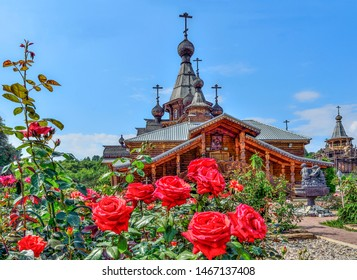 Novokuznetsk, ussia - July 29, 2019: Rose garden on front yard of Christian Temple of the Holy Martyr John the Warrior in Novokuznetsk, Russia. Beauty of nature and wooden architecture of Russia