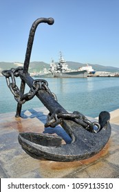 NOVOROSSIYSK, RUSSIA - April 29, 2017 Anchor - The Symbol of Sea Greatness. Anchor monument on the embankment of Novorossiysk in the background of the cruiser Mikhail Kutuzov.