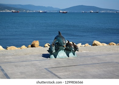Novorossiysk, Russia - July 3, 2018: The bronze sculpture of dolphins at the embankment against the sea on a sunny day