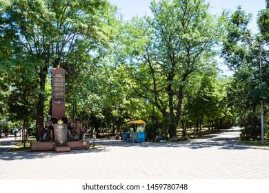 NOVOROSSIYSK, RUSSIA - JULY 7, 2019: people in green Park named after M Frunze and Monument to Novorossiysk residents fallen in undeclared wars in Novorossiysk city