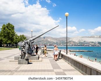 NOVOROSSIYSK, RUSSIA - JULY 7, 2019: tourists near memorial antiaircraft gun on Admiral Serebryakov Embankment. Novorossiysk is city in Krasnodar Krai, Russia, it is main country's port on Black Sea