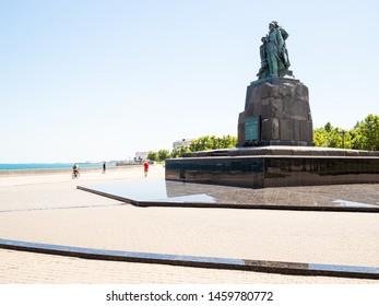 NOVOROSSIYSK, RUSSIA - JULY 7, 2019: people walk on Admiral Serebryakov Embankment and Monument to the Dead Fishermen of Seiner Urup on Cape of Love in Novorossiysk city