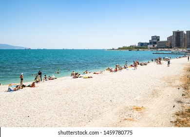 NOVOROSSIYSK, RUSSIA - JULY 7, 2019: tourists on white beach along Admiral Serebryakov Embankment in Novorossiysk. Novorossiysk is city in Krasnodar Krai, Russia, it is country's port on Black Sea